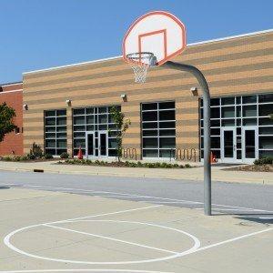 Schulgebäude mit Sportplatz: Mehr Freizeit in der Schule? Foto: Shutterstock