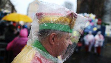 Ein Kölner Karnevalist mit Regenschutz am frühen Rosenmontag. Foto: dpa