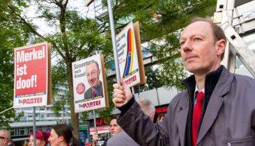 """Martin Sonneborn (rechts) und Mitglieder von """"Die Partei"""" demonstrieren in Berlin im Wahlkampf 2014 gegen die deutsche Kanzlerin Angela Merkel. Foto: dpa"""